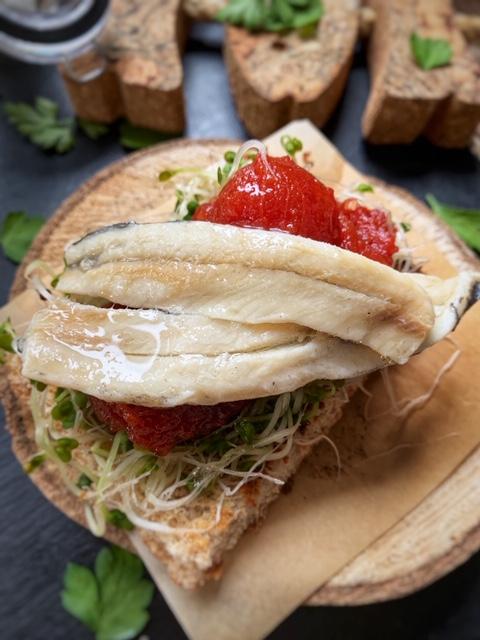 Tosta de boquerones en vinagre con tomate confitado y germinados